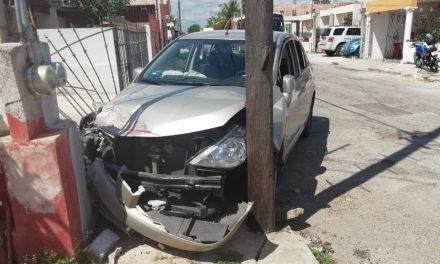 Saca auto de cochera y choca contra autobús, casa y poste