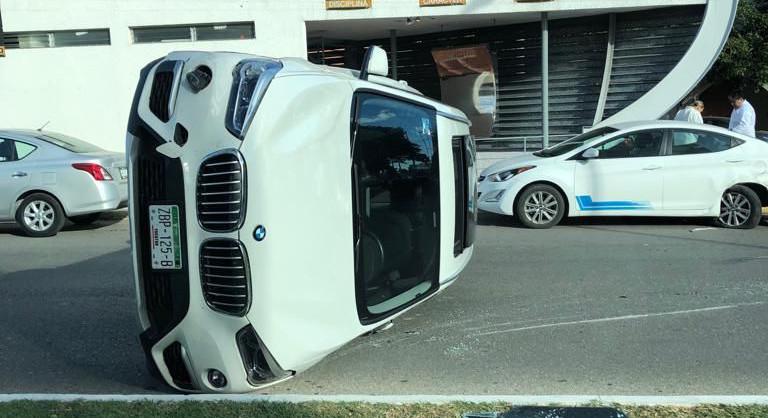 Lo distrae llamada de celular y vuelca en lujoso BMW